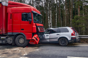 Silver car collision with a red truck