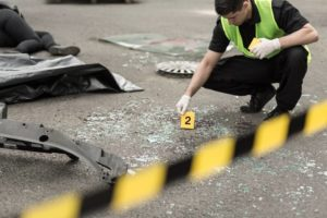 Man placing signs of ground for evidence after truck crash. Truck accident claims can be more complicated than car accident cases, in part because the evidence of liability can be so complex. Speak with a Spring, TX truck accident lawyer who can help as soon as possible.