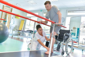 Injured man walking between parallel bars with the help of a physical therapist.